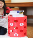 Rutgers-Otto-Storage-Stool-girl-sitting-next-to-it-on-floor